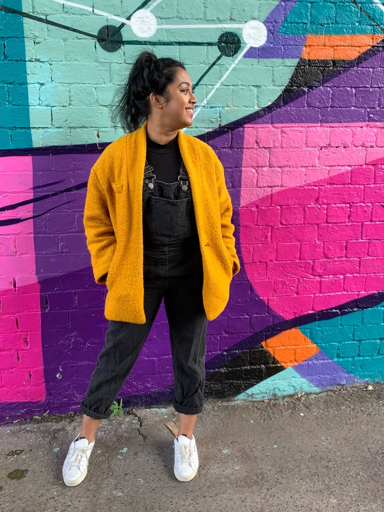 Picture of a woman in black dungarees, a yellow coat, and white trainers, in front of a wall with purple, pink, orange, and blue shapes