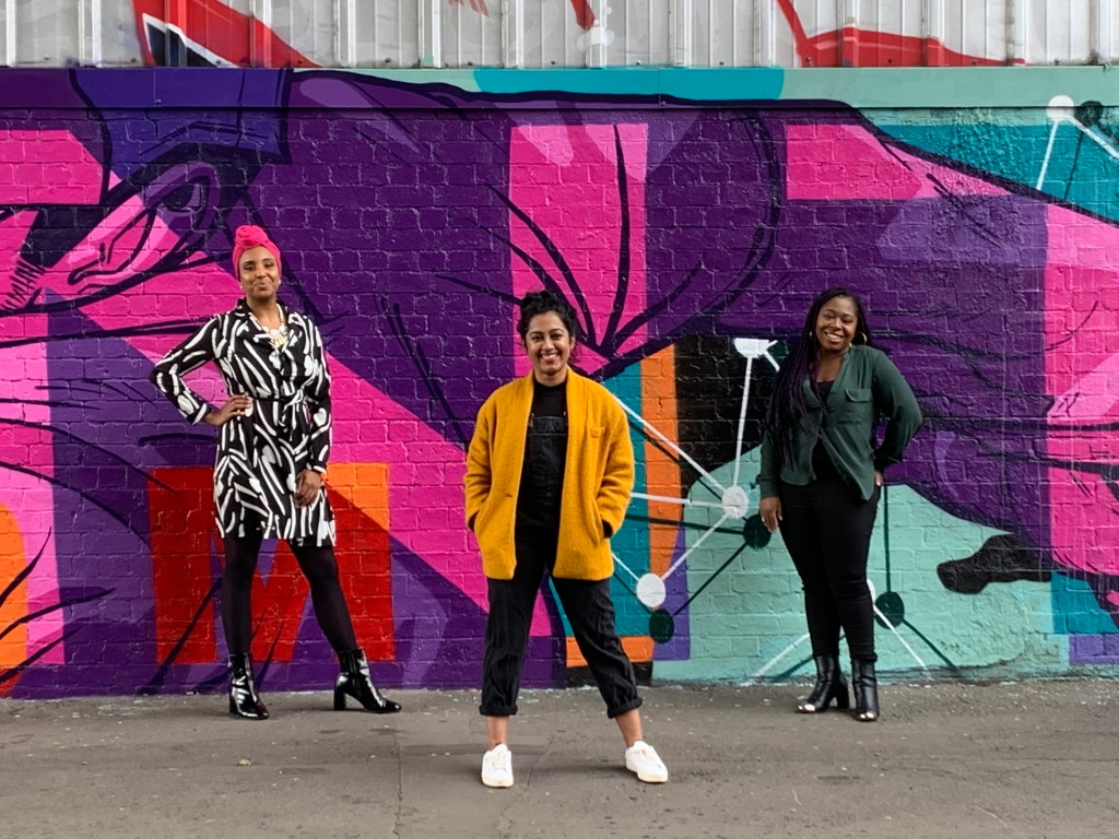 Picture of 3 women smiling and standing in front of a wall.